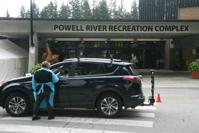 Healthcare worker helping person in car outside of Powell River Recreation Complex